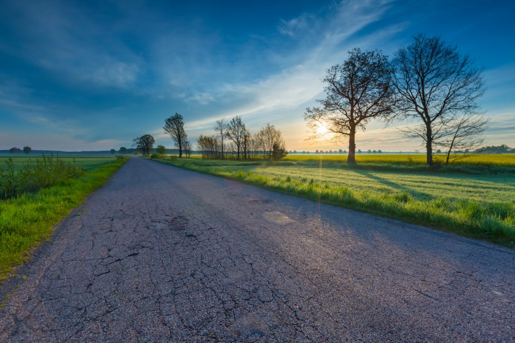 Rural destroyed asphalt road in calm countryside. Springtime landscape photographed in Poland.